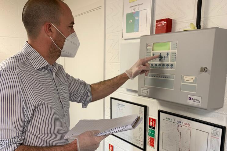 Electronic Security employee using fire alarm panel