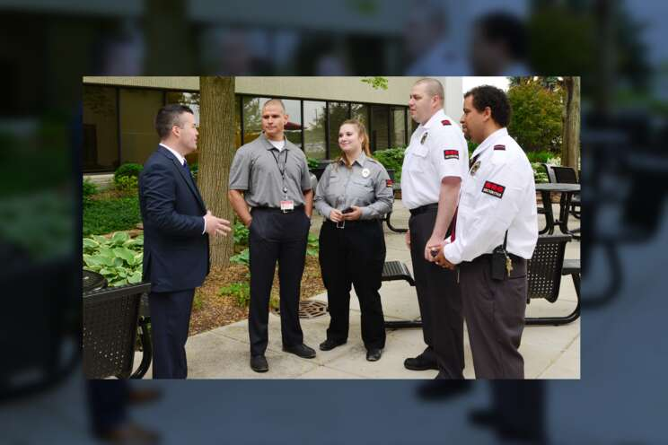 A group of Securitas officers speaking with a client.