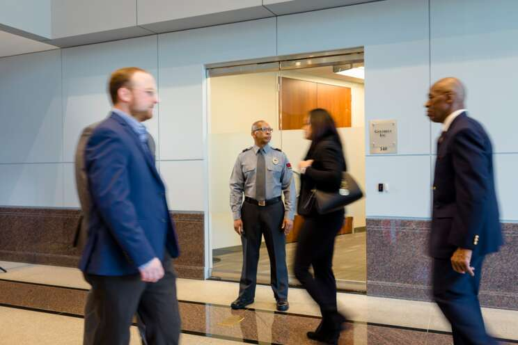Male security officer standing by an elevator observing people walking by.