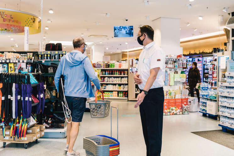 Sicherheitsmitarbeiter überwacht die Corona-Auflagen im Einzelhandel