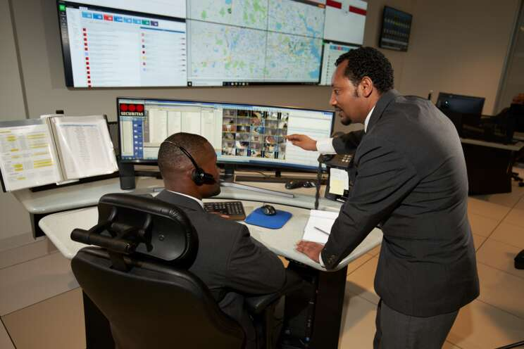 Two male security officers at the GSOC looking at computers.