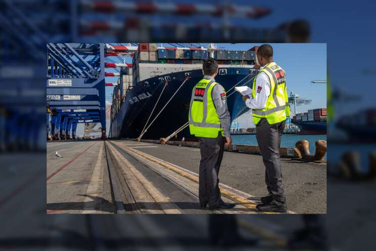 Two male security officers speaking on at a shipping dock.