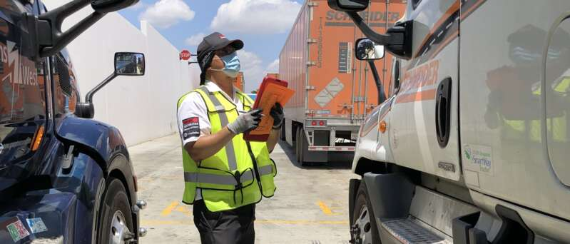 Female security officer with mask checking in trucks.