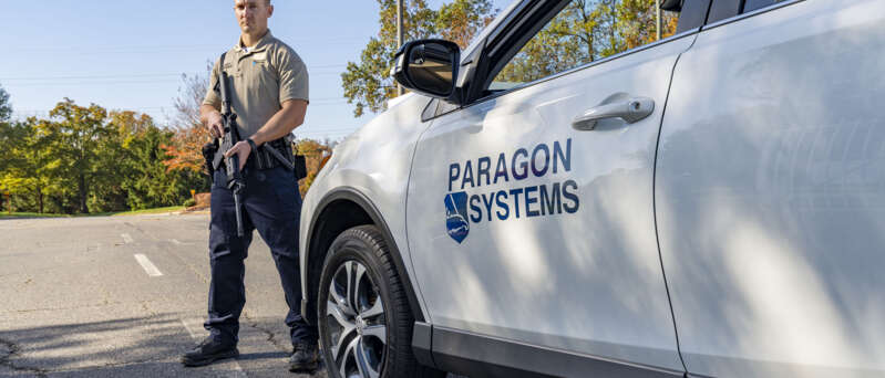 Armed Paragon Systems officer standing by his vehicle.
