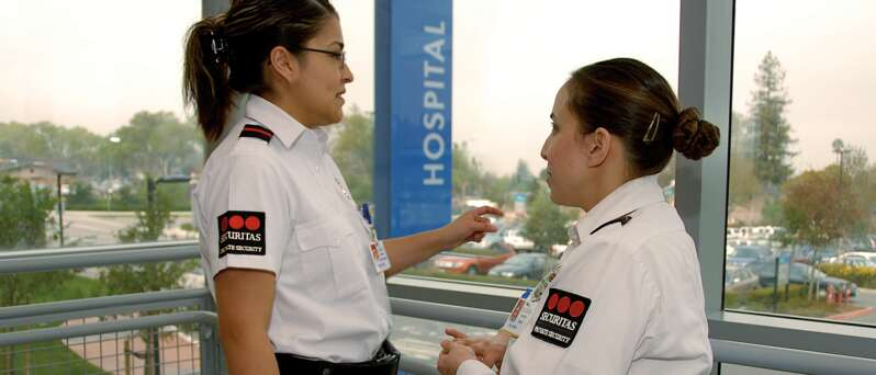 Two female healthcare security officers talking.